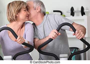 Man and woman on cross trainers kissing