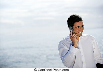 Man using his cellphone by the sea