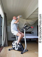 Man cycling on machine at home