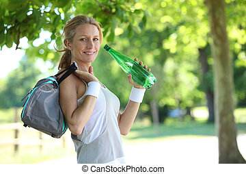 woman in fitness clothes drinking