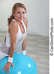 Woman balancing on inflatable gym ball