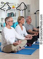Mature adults doing meditation