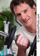 man working on his biceps in the gym