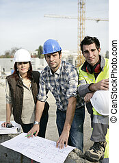 A team of tradespeople discussing a blueprint