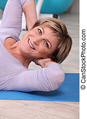 Woman doing sit-ups on a yoga mat