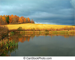 Fall landscape with field after harvest and a pond in the...