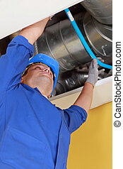 Plumber holding a blue flexible pipe under some air ducts