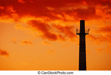 Industrial chimney at sunset