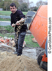 Laborer shoveling gravel into a mixer