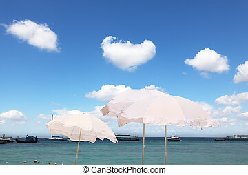 The white parasols on the sea breeze - Tropical blue sea....