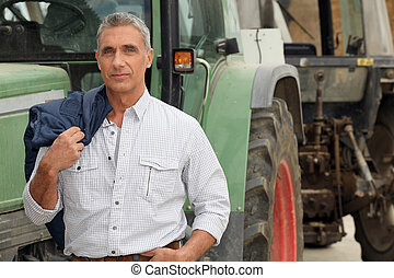 farmer posing in front of his tractor