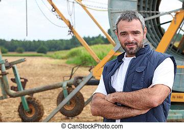 Farmer stood by irrigation system