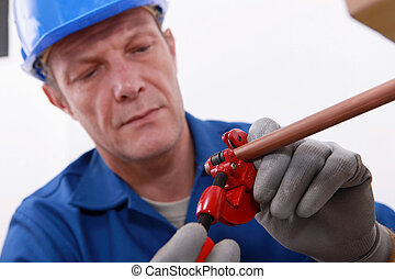plumber cutting a copper pipe with a pipe cutter