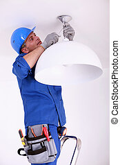 Electrician fitting a ceiling light