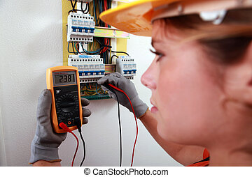 An electrician using a multimeter