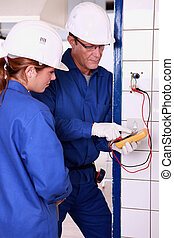 Electrician with female apprentice