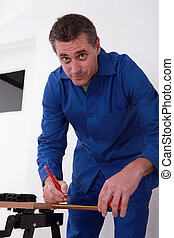 carpenter using a steel measuring tape for drawing a mark on...