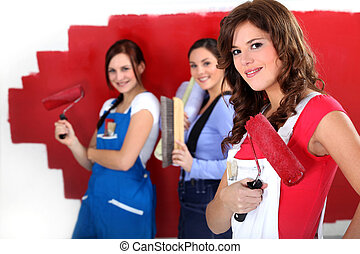 Three women painting a wall in red.
