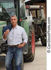 Farmer stood by tractor