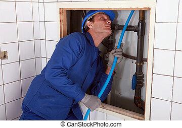 Plumber feeding blue pipe behind a wall