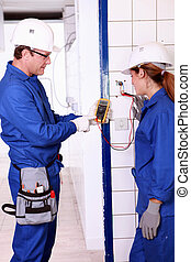 Supervisor explaining work to female electrician apprentice
