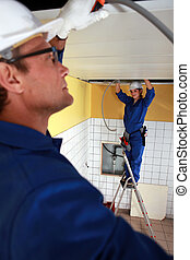 Electrical team wiring a tiled room