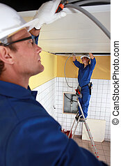 Laborers installing piping in ceiling