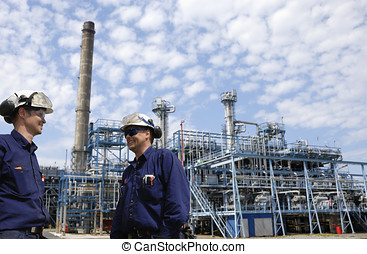 oil and gas workers with refinery - two refinery workers...