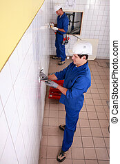 Top view of electricians in a tiled room