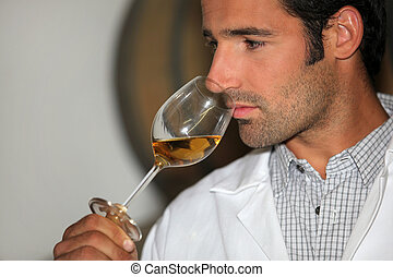 A man smelling wine
