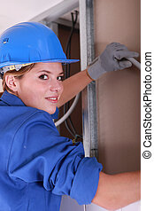 Attractive female electrician at work
