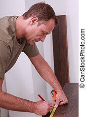 Man measuring laminate flooring