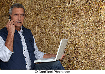 mature farmer on the phone with laptop against hay...
