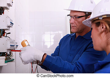Electricians fitting a fusebox