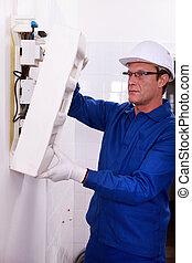 Man inspecting fuse box