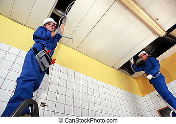 two electricians working in a building