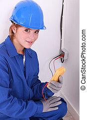 doe-eyed female electrician at work with tester