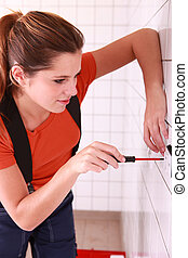 Female electrician installing a wall socket
