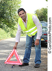 Man in fluorescent vest putting out a warning triangle by a...