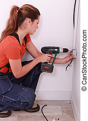 a female electrician working on an electrical outlet