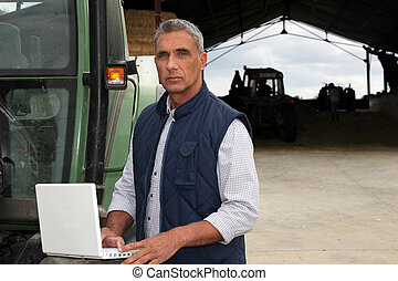 Farmer with laptop stood by tractor
