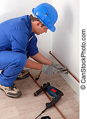 Plumber fixing copper pipe to wall