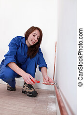 Tradeswoman fixing a copper tube against a wall