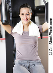 Young woman works out on weight-training machine