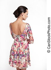 back of Young beautiful woman in colorful summer dress isolated on white