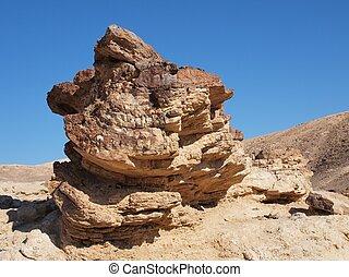 Scenic stratified orange rock in stone desert, Israel