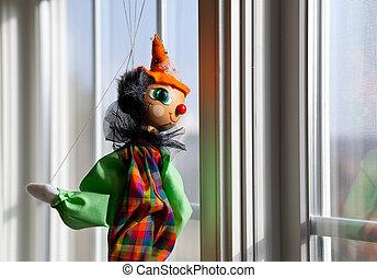 String puppet gazing outside window in sun