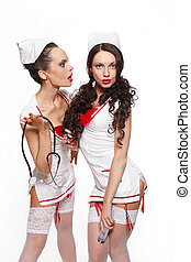 two sexy beautiful  female brunette doctors in red lingerie white stocking and red lips on a white background long curly hair with medicine equipment