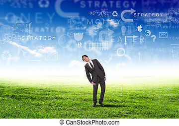 Young businessman outdoor with business symbols on the sky...