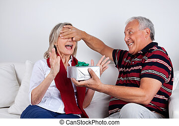 Senior Man Giving Gift to His Wife